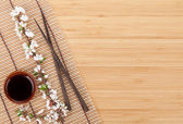 Chopsticks and sakura branch over bamboo mat — Stock Photo
