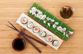 Sushi set with green tea and sakura branch — Stock Photo