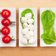 Tomatoes, mozzarella and green salad leaves — Stock Photo #50923137