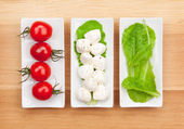 Tomatoes, mozzarella and green salad leaves — Foto de Stock