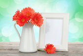 Orange gerbera flowers and photo frame on wooden table — Stock Photo