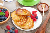 Pancakes with raspberry, blueberry, mint and honey syrup — Stock Photo