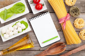 Tomatoes, mozzarella, pasta and green salad leaves with notepad  — Stock Photo