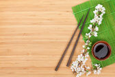Chopsticks, sakura branch, soy sauce — Stockfoto