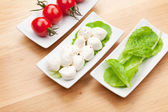 Tomatoes, mozzarella and salad leaves — Stock Photo