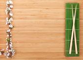 Chopsticks and sakura branch — Stock Photo
