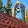 Foto de Stock  : Bell on church rooftop covered with orange tiles