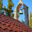 Stock Photo: Bell on church rooftop covered with orange tiles