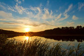 Beautiful sunset over the forest lake — Stock Photo