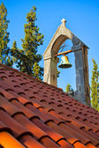 Bell on the church rooftop covered with orange tiles — Stock Photo