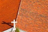 Cross on the church rooftop covered with orange tiles — Zdjęcie stockowe