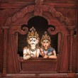 Shiva and Parvati wooden figures in the window of Shiva Parvati Hindu temple at Durbar Square - Stock Photo