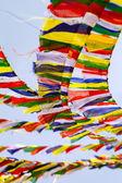 Buddhist Tibetan prayer flags against blue sky background — Stock Photo