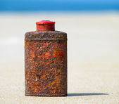Old rusty metal bottle on the beach — Stock Photo