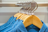 Jeans shirts on the hangers in the clothing store — Zdjęcie stockowe