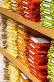 Neat stacks of folded clothing on the shop shelves — Stock Photo