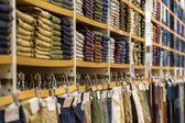 úhledné hromádky složené oblečení na pultech — Stock fotografie