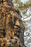 Stone face on the towers of ancient Bayon Temple in Angkor Thom — Stock Photo