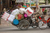 Plastic ware vendor on bicycle — Photo