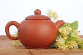 Earthenware teapot with linden tea and flowers on white background — Stock Photo