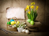 Colorful easter eggs in brown basket — Stock Photo
