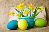 Easter eggs and daffodils in a basket — Stock Photo