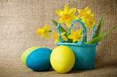 Easter eggs and daffodils in a basket — Photo