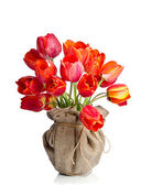 Red tulips vase wrapped in burlap on white background — Stockfoto