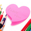 Colored pencils and a sheet of paper in the shape of a heart wit — Stock Photo #48164729