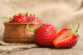 Ripe Strawberry in a wooden Bowl on burlap background — Stok fotoğraf