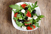 Greek salad in white salad bowl on the table — Stock Photo