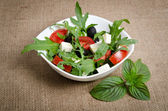 Greek salad in white salad bowl on sacking — Stockfoto