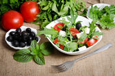 Greek salad in white salad bowl with cutlery and vegetables — Stock Photo