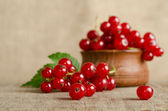 Red currant in wooden plate on the table — Stock Photo