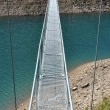 Alpine footbridge over lake — Stock Photo