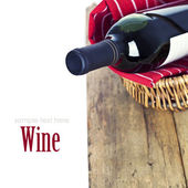 Bottle of red wine in basket — Stock Photo