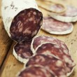 Traditional sliced meat sausage salami on wooden board - Stock Photo