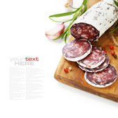 Traditional sliced meat sausage salami on wooden board — Stock Photo