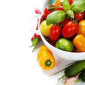 Assorted tomatoes and vegetables in colander — Stock Photo