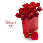 Valentine composition with shopping bag and red tulips — Stock Photo