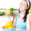 Smiling woman with orange juice in the kitchen — Stock Photo #41435363