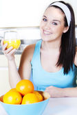 Smiling woman with orange juice in the kitchen — Stok fotoğraf