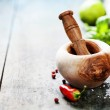 Wooden Mortar and Pestle and chilli peppers, herbs and spices — Stock Photo #46930977