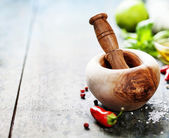 Wooden Mortar and Pestle and chilli peppers, herbs and spices — Stock Photo