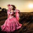 Stock Photo: Attractive romantic woman on beautiful pink dress pose outdoor.