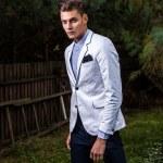 Portrait of young beautiful fashionable man against autumn garden. — Stockfoto #13149679
