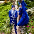 Couple in expensive dark blue costume of illusionist pose in fairy tale flowers park. — Stock Photo