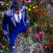 Man in expensive dark blue suit of illusionist pose on flower meadow. — Stock Photo