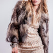 Portrait of attractive stylish woman in fur against grey background. - Stock Photo