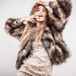 Portrait of attractive stylish woman in fur against grey background. — Stock Photo #18351587